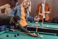 jeunes amis attirants de multiculture jouant dans la piscine Photo libre de droits