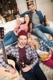 Jeunes amis avec de la bière potable de guitare et sourire à l'appareil-photo Image stock