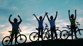 Jeunes amis avec des bicyclettes sur le fond de ciel banque de vidéos