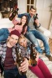 Jeunes amis avec des bouteilles à bière souriant à l'appareil-photo à la maison Images stock