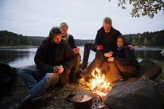 Jeunes amis avec des tasses de café se reposant près du feu de camp Photographie stock
