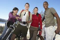 Jeunes amis avec des vélos de montagne par le lac Photo libre de droits