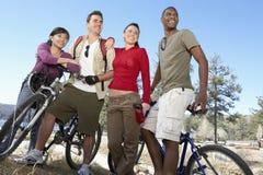 Jeunes amis avec des vélos de montagne par le lac Photographie stock
