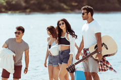 Jeunes amis avec la guitare passant le temps ensemble et marchant sur la rive Photo stock