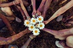 Jeunes amis avec la peinture colorée sur des corps tenant des camomilles au festival de holi Images stock