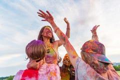 Jeunes amis avec les mains tendues ayant l'amusement ensemble au festival de holi Photos stock