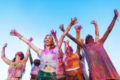 Jeunes amis avec les mains tendues ayant l'amusement ensemble au festival de holi Photo libre de droits