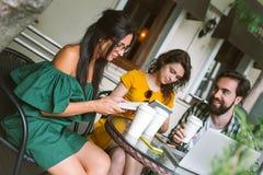 Jeunes amis avec les smartphones et l'ordinateur portable en café avec du café Image libre de droits