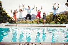 Jeunes amis ayant l'amusement à la piscine Images stock