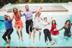 Jeunes amis ayant l'amusement à la piscine Photo stock