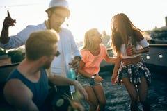 Jeunes amis ayant l'amusement à une partie de dessus de toit, jouant la guitare, le chant, la danse et le boire photos libres de droits