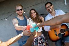Jeunes amis ayant l'amusement à une partie de dessus de toit, jouant la guitare, le chant, la danse et le boire images stock