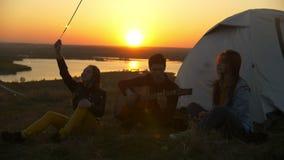 Jeunes amis ayant l'amusement avec des cierges magiques et les chansons avec la guitare au coucher du soleil dehors clips vidéos