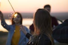 Jeunes amis ayant l'amusement avec des cierges magiques sur la colline à l'été su Photographie stock libre de droits