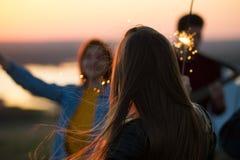 Jeunes amis ayant l'amusement avec des cierges magiques sur la colline à l'été su Images stock