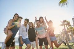 Jeunes amis ayant l'amusement ensemble au soleil dehors Photo stock