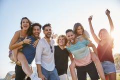 Jeunes amis ayant l'amusement ensemble dehors au soleil Photographie stock libre de droits