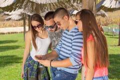 Jeunes amis ayant l'amusement et jouant avec le téléphone dehors Photographie stock