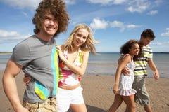 Jeunes amis ayant l'amusement sur la plage d'été Photographie stock libre de droits