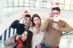 Jeunes amis ayant l'amusement tenant la moustache artificielle d'hiver Photographie stock libre de droits