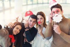 Jeunes amis ayant l'amusement tenant la moustache artificielle d'hiver Photographie stock
