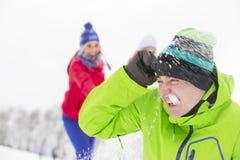 Jeunes amis ayant le combat de boule de neige Image stock