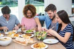 Jeunes amis ayant le repas à la table Photos libres de droits