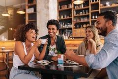 Jeunes amis ayant un grand temps en café Images stock