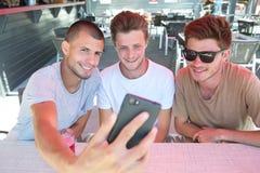 Jeunes amis beaux de groupe faisant le selfie Photos stock