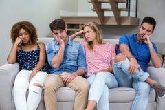 Jeunes amis bouleversés s'asseyant sur le sofa Image stock