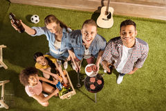 Jeunes amis buvant de la bière et faisant le barbecue souriant à l'appareil-photo Photographie stock