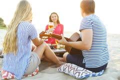 Jeunes amis buvant du vin rosé sur le pique-nique de plage d'été Images stock
