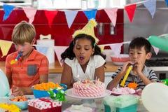 Jeunes amis célébrant l'anniversaire dans la cuisine Image stock