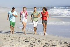 Jeunes amis courant le long de la plage Photographie stock libre de droits
