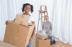 Jeunes amis déballant dans leur nouvelle maison et souriant à l'appareil-photo Photos stock