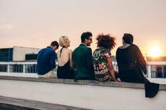 Jeunes amis détendant sur la terrasse pendant le coucher du soleil Image libre de droits