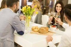 Jeunes amis dînant à la maison et grillant avec du vin blanc Photo stock