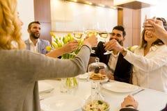 Jeunes amis dînant à la maison et grillant avec du vin blanc Image stock
