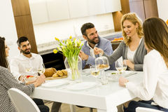 Jeunes amis dînant à la maison et grillant avec du vin blanc Image libre de droits