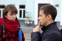 Jeunes amis d'étudiant parlant à l'université Essai de fille pour prouver quelque chose dirigeant le doigt Photographie stock