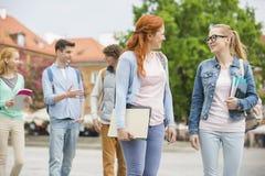 Jeunes amis d'université marchant sur la rue Photo stock