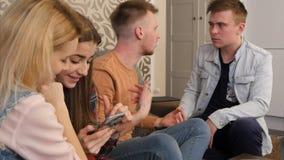 Jeunes amis d'université se réunissant dans une maison d'étudiant, parlant et à l'aide des smartphones Image stock