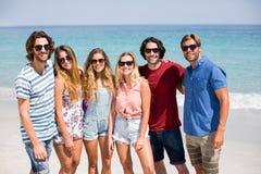 Jeunes amis dans des lunettes de soleil à la plage le jour ensoleillé Images libres de droits