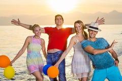 Jeunes amis dans des poses heureuses aléatoires à la plage Image libre de droits