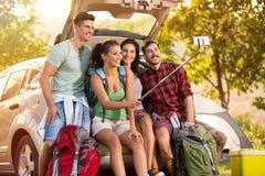 Jeunes amis dans la campagne sur des vacances en camping prenant le selfie Images stock
