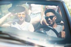 Jeunes amis dans la voiture de cabriolet prête à vacation Photos libres de droits