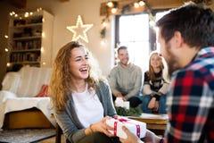 Jeunes amis dans le salon décoré célébrant le pouvoir adiathermique de Noël Photo stock