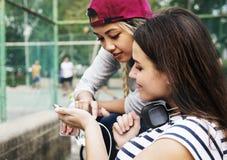 Jeunes amis de femelle adulte écoutant la musique par leur smar Images stock