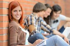 Jeunes amis de femme d'étudiant s'asseyant à l'arrière-plan Image libre de droits