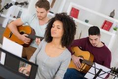 Jeunes amis de groupe jouant la guitare Images stock